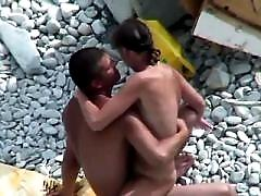 Wet and nude babe gives blowjob to her guy on a beach
